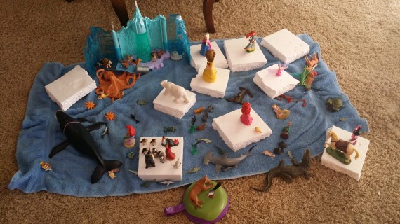 "Imaginary play with dolls and figurines. Those are styrofoam ""ice burgs"" on a blue towel ""ocean."""