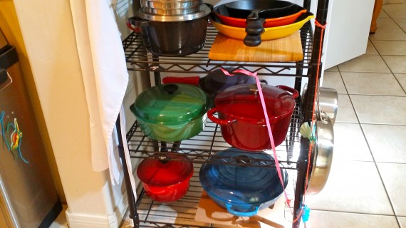 My collection of Le Creuset pans on a rack complete with Kamea's toys hanging on it.