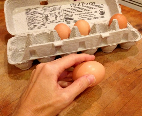 Cracking a pastured organic egg on a flat surface.