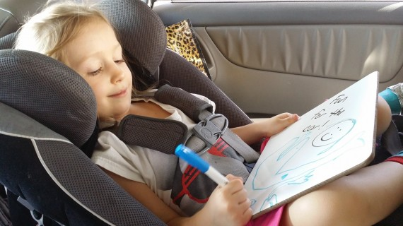 Drawing in the car on a dry erase whiteboard. Yes, she's still rear facing. #SafetyFirst
