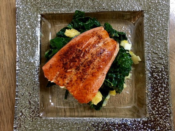 Wild-caught pan-roasted salmon over braised kale.